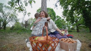 stock-footage-young-attractive-woman-with-her-son-on-a-picnic-the-boy-runs-to-his-mother-hugging-her-and