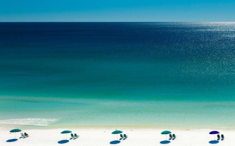 Beach umbrellas and deck chairs on beach, Destin, Florida, USA